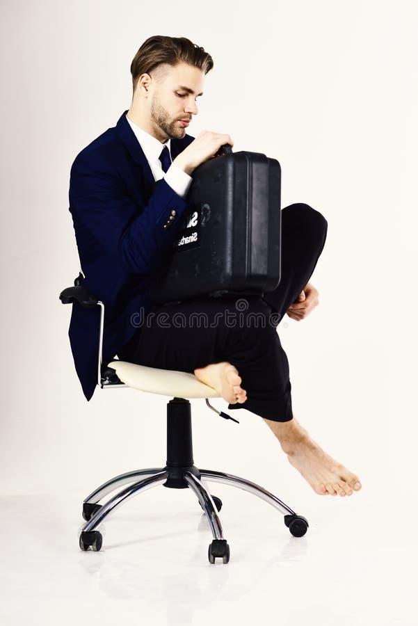 Mann in der intelligenten Klage sitzt und hält Fall Schreiben Sie Schulden, Betriebsmittelkredit, Konkurskonzept gut lizenzfreie stockfotos