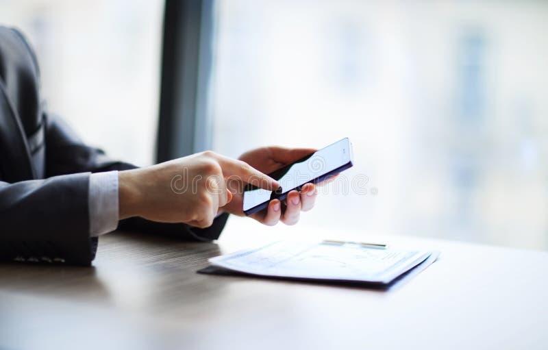 Mann, der intelligentes Mobiltelefon im Büro verwendet lizenzfreies stockbild