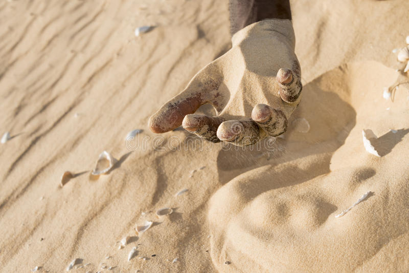 Mann, der irgendeinen Sand in der Hand hält lizenzfreies stockfoto