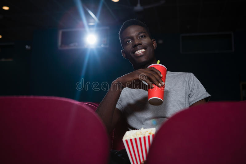 Mann, der Kältegetränke beim Aufpassen des Films hat lizenzfreie stockbilder