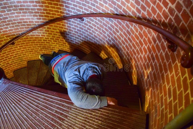 Mann, der kämpft, um Wendeltreppe zu klettern stockfotos