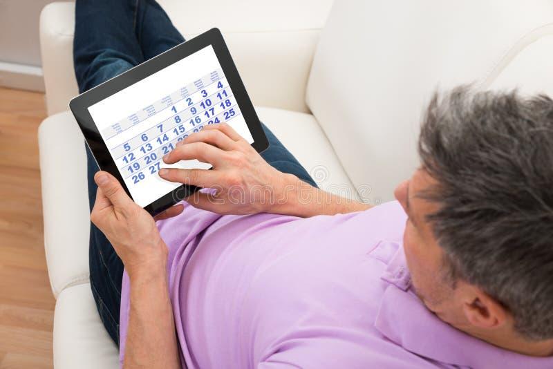 Mann, der Kalender in der digitalen Tablette betrachtet lizenzfreies stockfoto