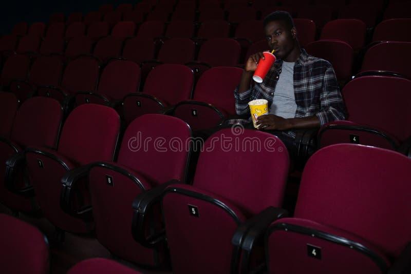 Mann, der kaltes Getränk beim Aufpassen des Films hat stockfotografie