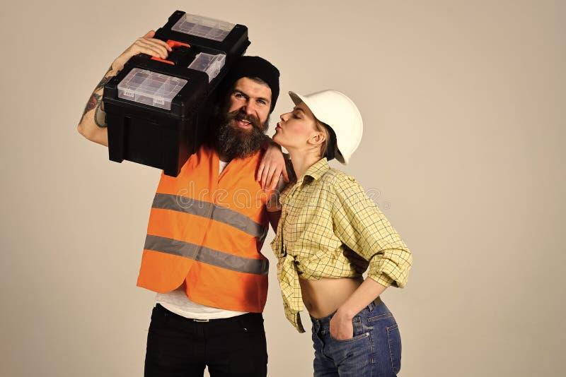 Mann, der Kamera betrachtet Hausfrau, die mit Schlosser mit Werkzeugkasten flirtet Mädchen mit Sturzhelm auf küssendem Gesicht na lizenzfreie stockfotografie