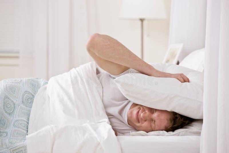 Mann, der Kissen verwendet, um Geräusche heraus zu blocken lizenzfreies stockbild