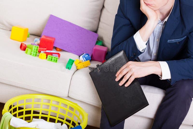 Mann in der Klage, die auf Sofa sitzt stockfotografie