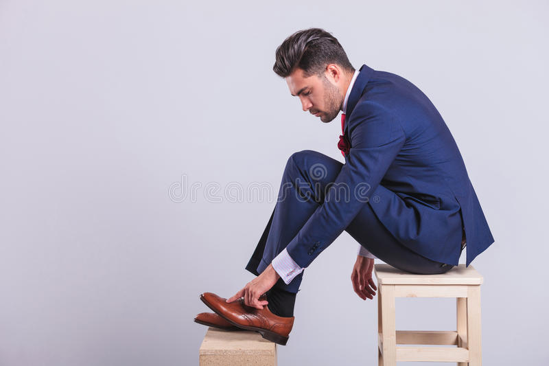 Mann in der Klage, die auf Stuhl im Studio säubert seine Schuhe sitzt lizenzfreie stockbilder