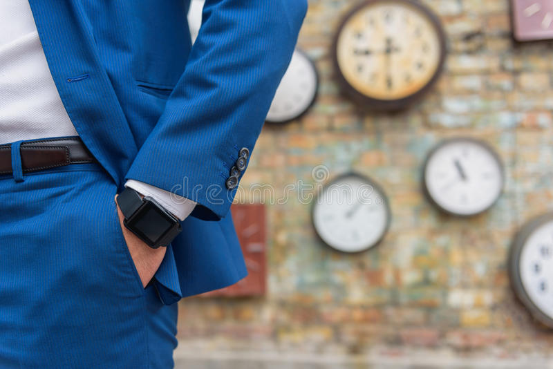 Mann in der Klage, die nahe Wand mit Uhren steht stockbild