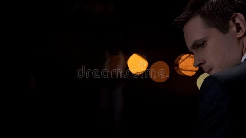 Mann in der Klage ernste Entscheidungen nachts denkend, Stadtlichter auf Hintergrund lizenzfreies stockfoto