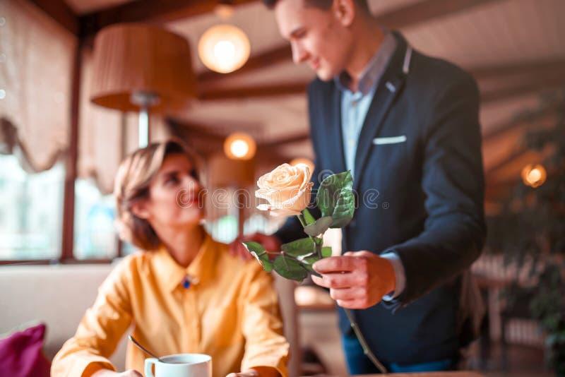 Mann in der Klage gibt der jungen glücklichen Frau rosafarbene Blume lizenzfreie stockfotografie