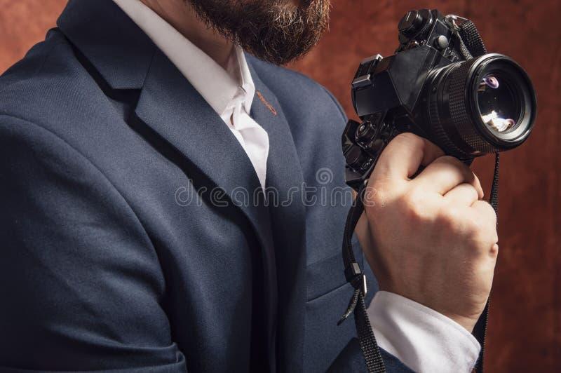 Mann in der Klage hält alte Kamera stockfoto