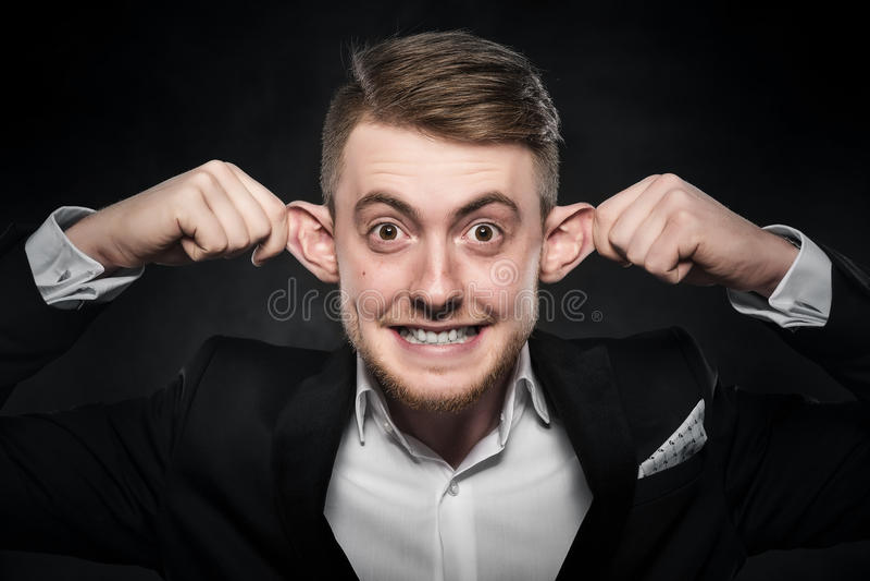 Mann in der Klage macht lustiges Gesicht stockfotografie