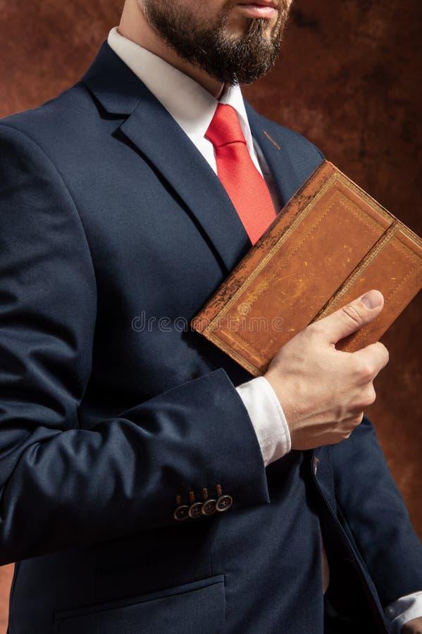 Mann in der Klage steht mit altem Buch lizenzfreies stockfoto