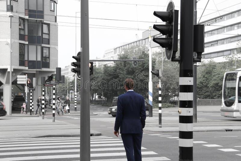 Mann in der Klage, welche die Straße kreuzt stockbild