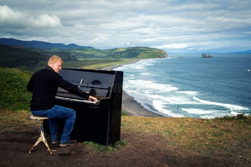Mann, der Klavier auf der Küste von Pazifischem Ozean spielt stockfotografie