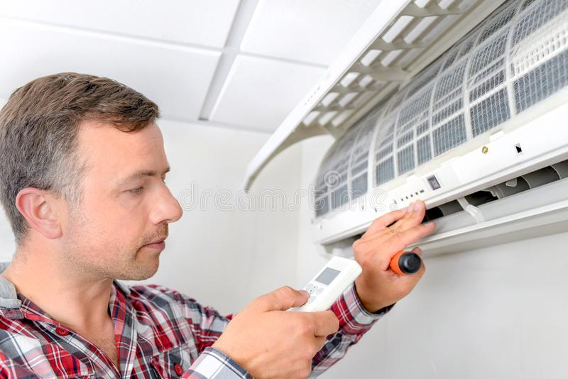Mann, der Klimaanlage überprüft stockbild