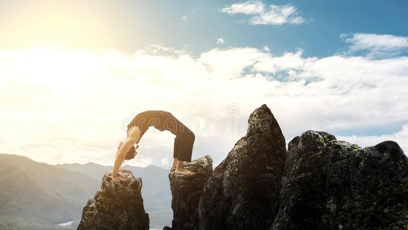 Mann, der komplexen Yogaübung Headstand tut Erstaunliche Yogalandschaft in den schönen Bergen Gefährliches Bremsungen traceur lizenzfreies stockbild