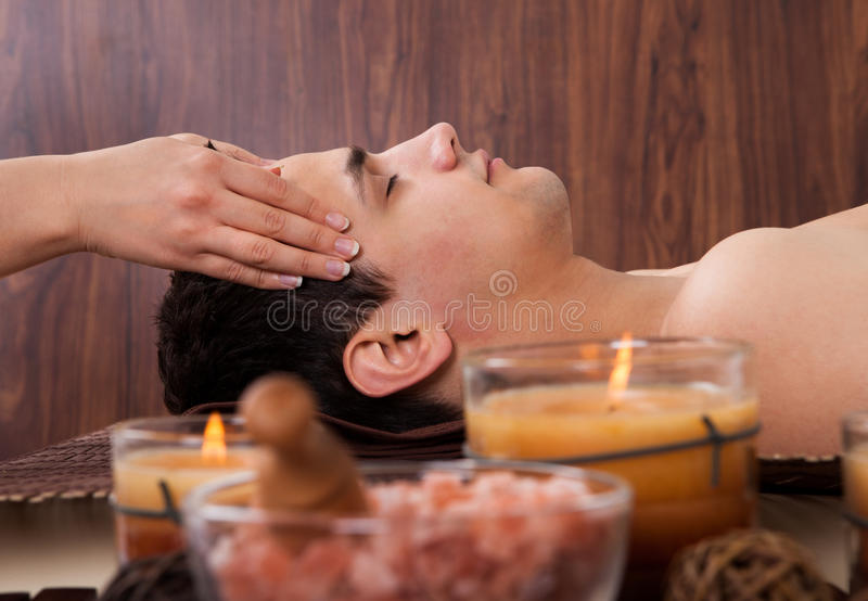 Mann, der Kopfmassage vom Massager im Badekurort empfängt lizenzfreies stockbild