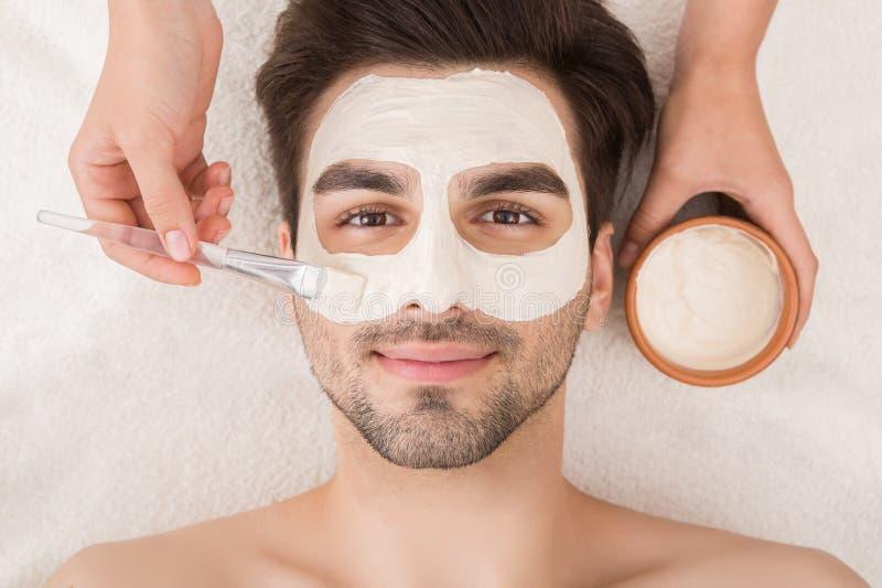 Mann, der kosmetische Maske im Badekurortsalon hat stockfoto