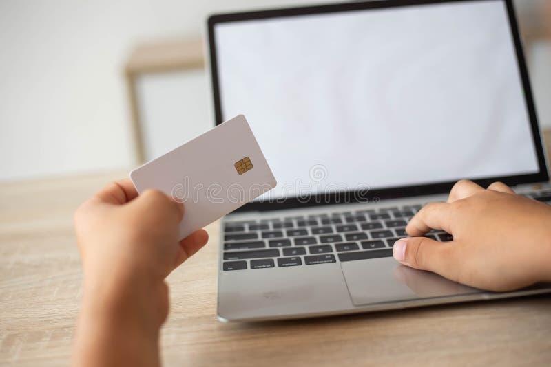 Mann, der Kreditkarte h?lt und Handy verwendet stockfoto