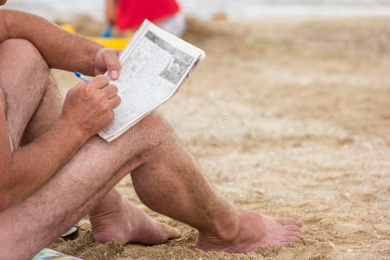 Mann, der Kreuzworträtsel sitzt und löst stockbilder