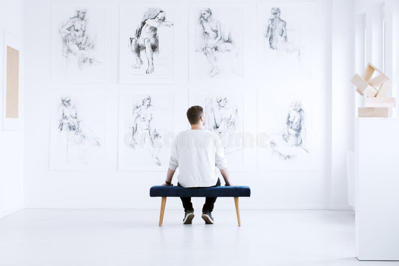 Mann, der in der Kunstgalerie sich entspannt lizenzfreie stockfotos