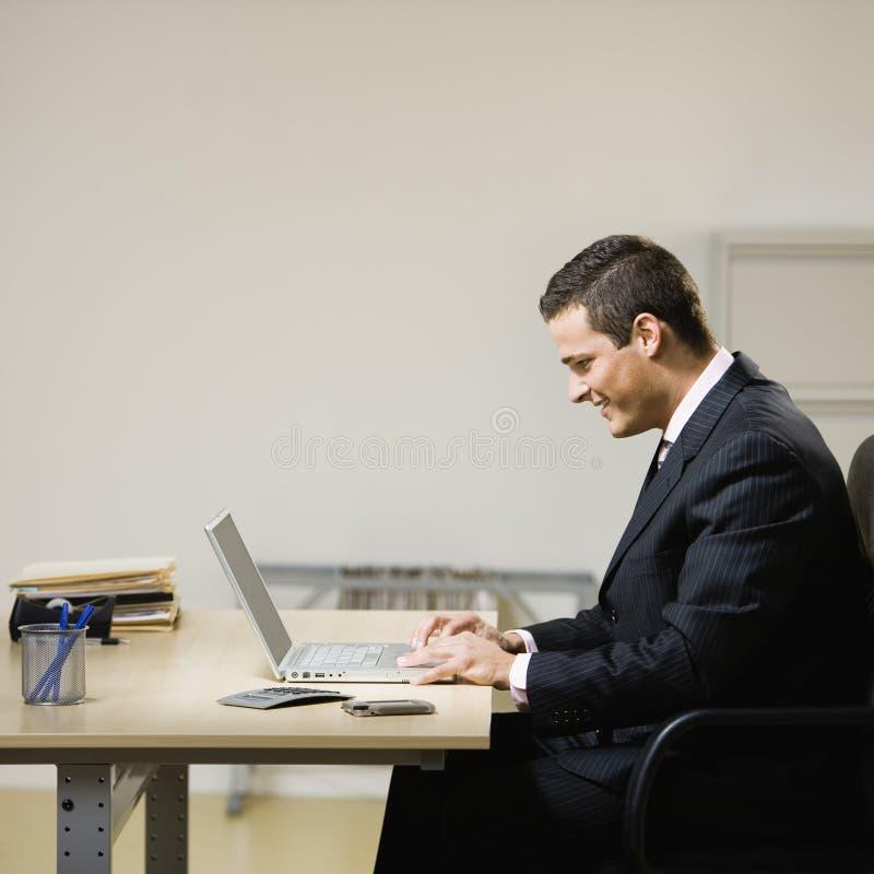 Mann, der an Laptop arbeitet stockfotografie