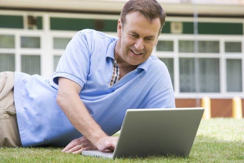 Mann, der Laptop beim Lügen im Gras auf Campus verwendet stockfotos