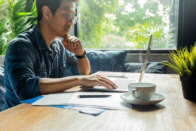 Mann, der an Laptop mit Dokumentenpapier und Kaffeetasse auf hölzernem Schreibtisch arbeitet stockfotografie