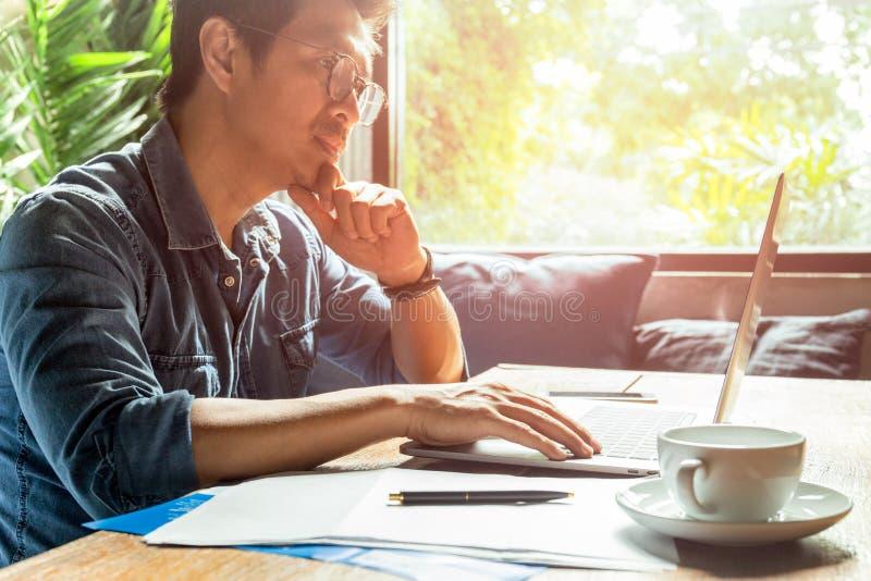 Mann, der an Laptop mit Dokumentenpapier und Kaffeetasse auf hölzernem Schreibtisch arbeitet stockfoto