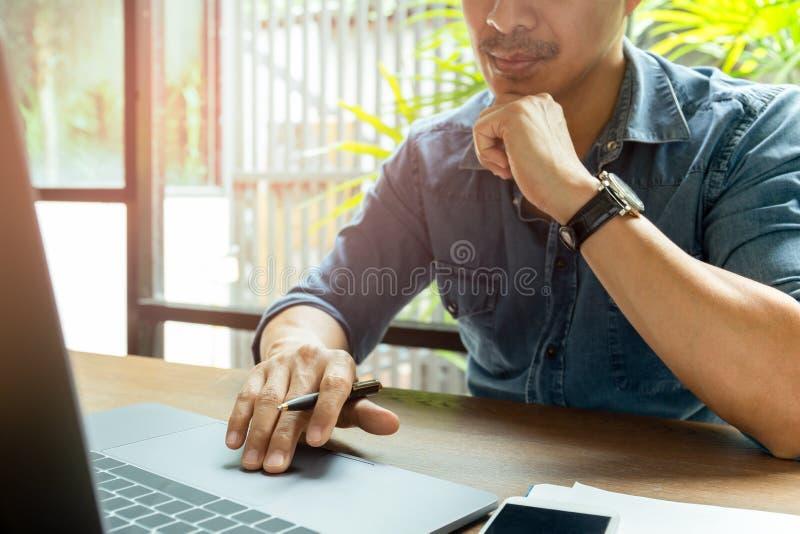 Mann, der an Laptop mit Handy auf hölzernem Schreibtisch arbeitet lizenzfreie stockfotografie