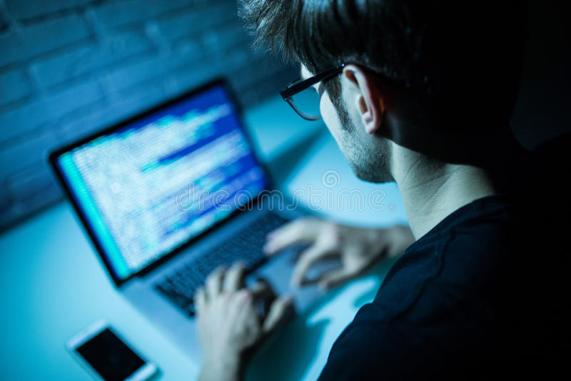 Mann, der Laptopschreibensprogrammiercode auf Laptop verwendet Junges hacke stockbild