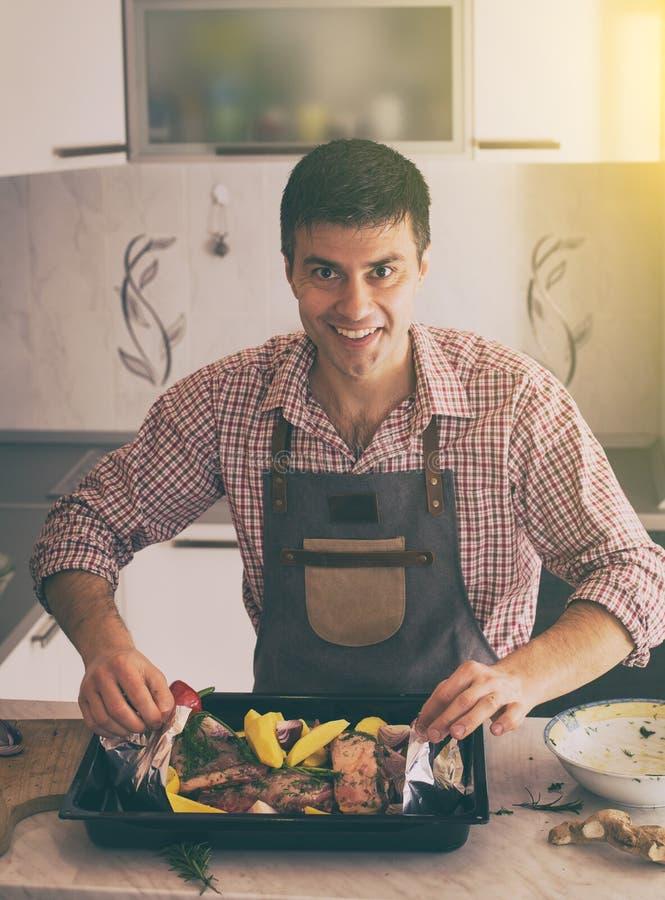 Mann, der Lebensmittel in der K?che zubereitet lizenzfreie stockfotos