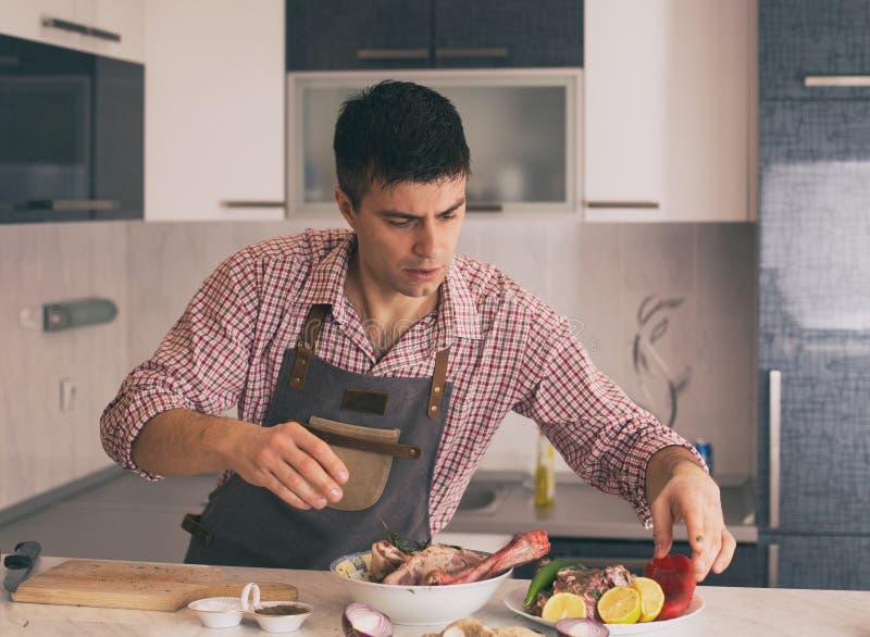 Mann, der Lebensmittel in der K?che zubereitet stockbilder