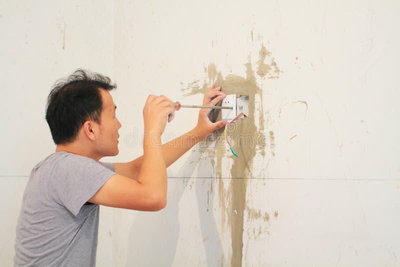 Mann, der Lichtschalter installiert stockbilder