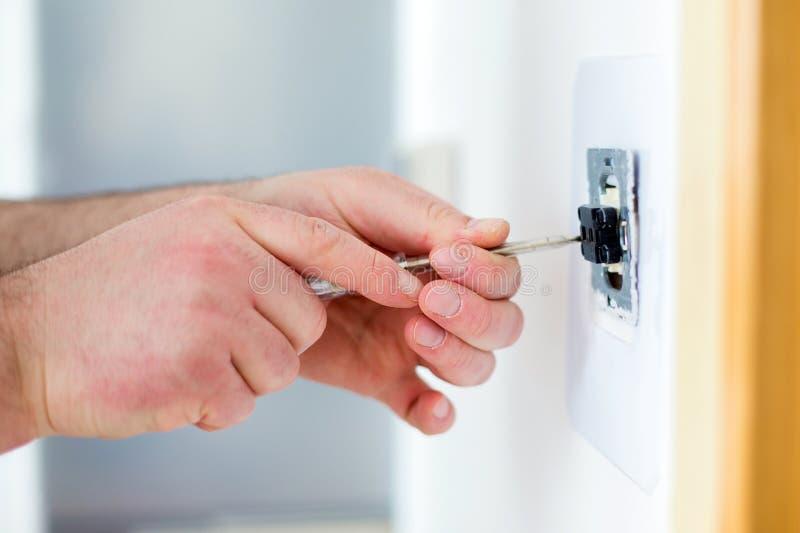Mann, der Lichtschalter mit Schraubenzieher installiert lizenzfreie stockfotos