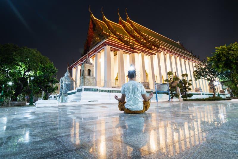 Mann, der in der Lotoshaltung in Wat Suthat Thepwararam nachts, Reflexion in den Bodenmarmorfliesen meditiert stockfotografie