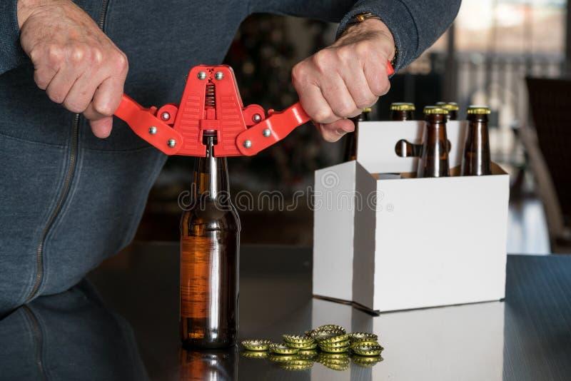 Mann, der Mützenmacher verwendet, um Metallkappen auf Bierflasche zu setzen stockbilder
