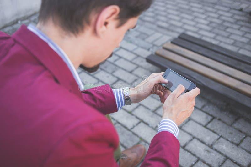 Mann in der magentaroten Anzugs-Jacke, die Smartphone mit beiden Händen hält stockfotos