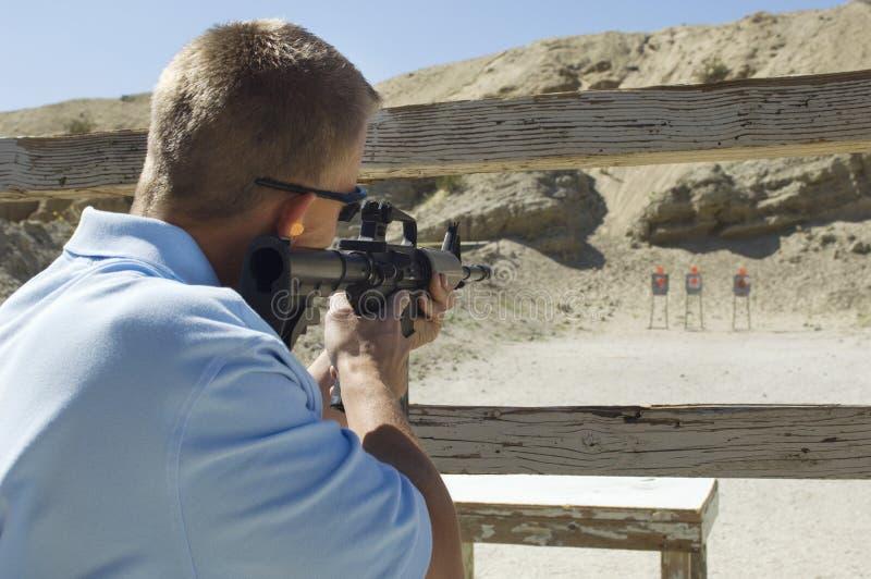 Mann, der Maschinengewehr auf Schießstand abzielt stockfotos