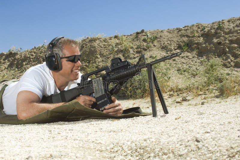 Mann, der Maschinengewehr zielt stockbild