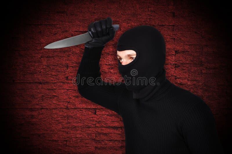Mann in der Maske mit Messer stockfotografie