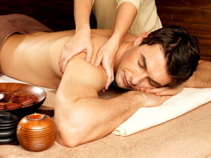 Mann, der Massage im Badekurortsalon hat stockbilder
