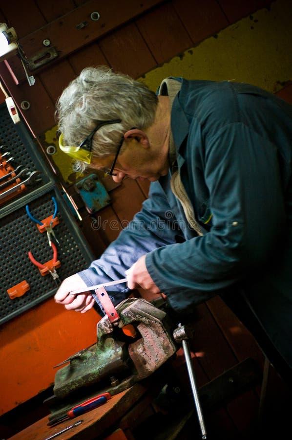 Mann in der Metallwerkstatt, die an Metallstück arbeitet stockbilder