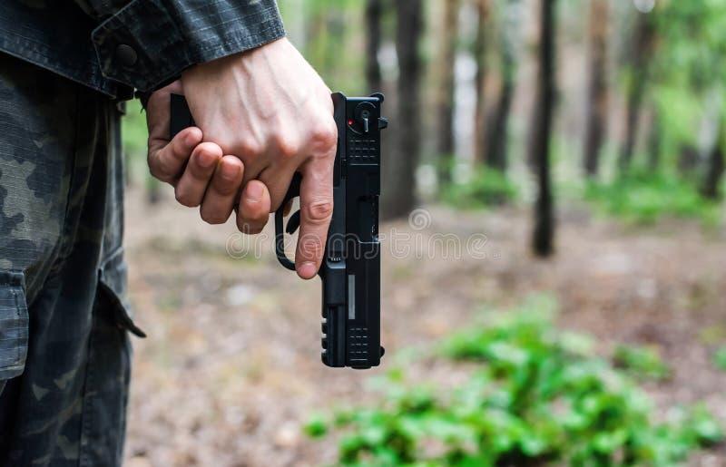 Mann in der Milit?rkleidung, die nach unten ein Gewehr h?lt stockfotos