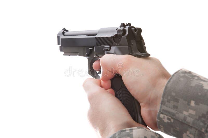 Mann in der Militäruniform, die Faustfeuerwaffe hält lizenzfreie stockfotos