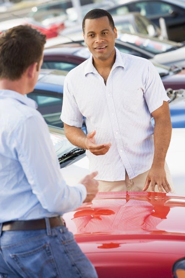 Mann, der mit Autoverkäufer spricht stockbild
