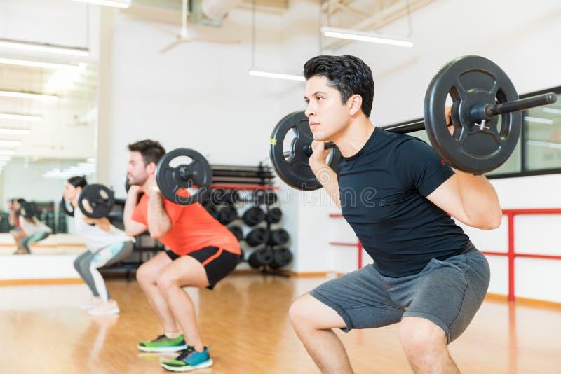 Mann, der mit Barbell im Fitnessstudio trainiert stockbild