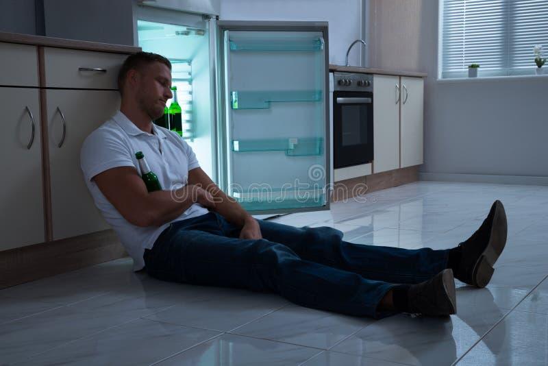 Mann, der mit Bierflasche schläft lizenzfreies stockfoto