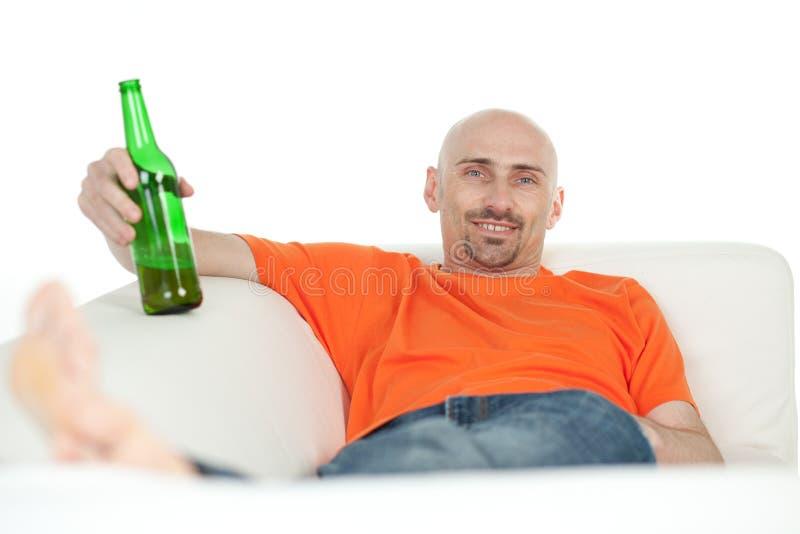 Mann, der mit Bierflasche sich entspannt stockfotografie